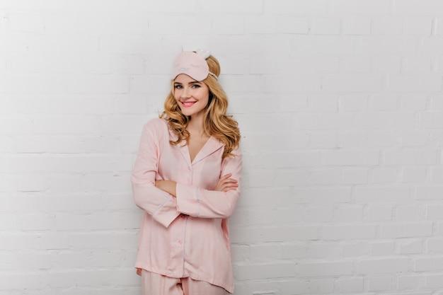 Blije krullende vrouw in zijden pyjama die zich in zelfverzekerde houding bevindt in de buurt van dichtgemetselde muur. positieve dame die in oogmasker op witte muur glimlacht.