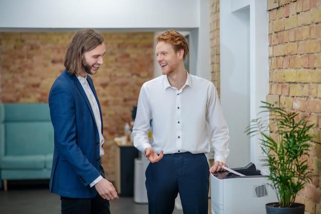 Blije lachende jonge volwassen mannelijke collega's in zakelijke kleding communiceren in kantoor gang