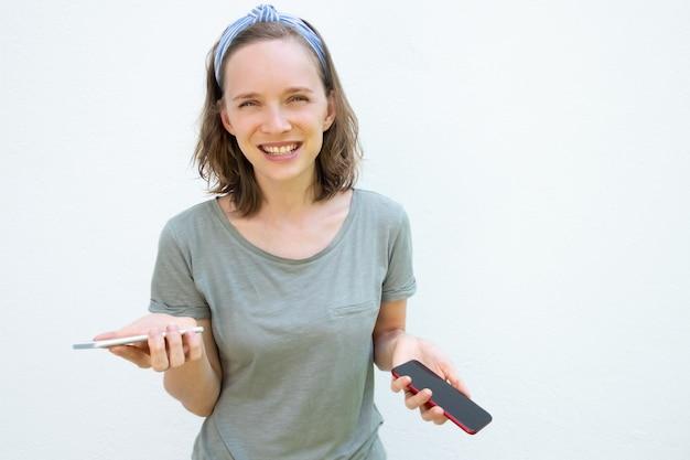 Blije lachende jonge vrouw met telefoons in beide handen