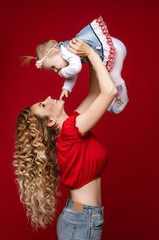 Blije langharige vrouw die lacht terwijl ze haar babymeisje in de lucht steekt.