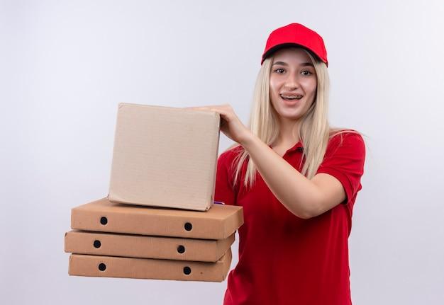 Blije leverings jonge vrouw die rode t-shirt en pet in de doos van de tandsteunholding en pizzadoos op geïsoleerde witte muur dragen
