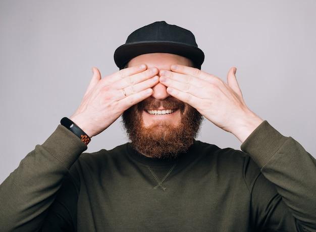 Blije man bedekt zijn eigen ogen met handen alsof hij op een verrassing wacht.