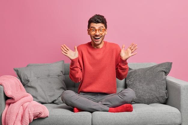 Blije man heft handpalmen op reageert op geweldig nieuws zit gekruiste benen op een comfortabele bank