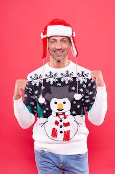 Blije man in wintertrui en hoed die vakantie n rode achtergrond viert, kerstmis.