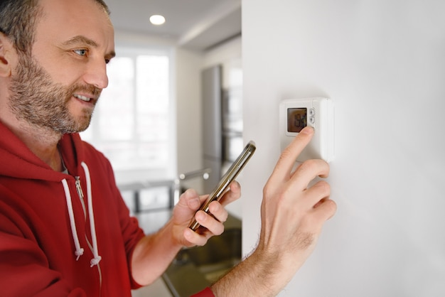 Blije man kijkt naar zijn smartphone hoe de temperatuur van de kachel in een smart home wordt geregeld
