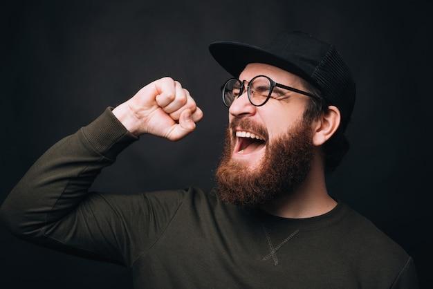 Blije man schreeuwt of zingt omdat hij won, hij maakt ook het winnaargebaar.