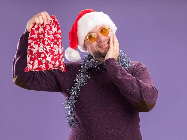 Blije man van middelbare leeftijd met een kerstmuts en een klatergoudslinger om de nek met een bril met een kerstcadeauzak die naar de zijkant kijkt en de hand op het gezicht houdt geïsoleerd op paarse achtergrond