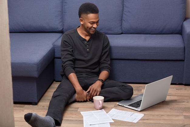Blije mannelijke freelancer met een donkere huidskleur poseert op de vloer bij de bank, bekijkt video op een laptopcomputer en werkt met papieren