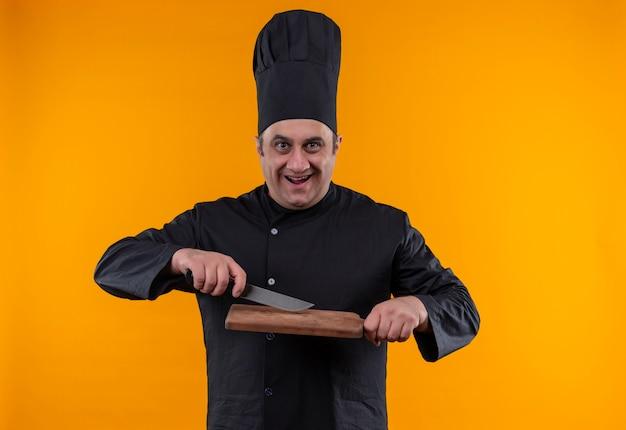 Blije mannelijke kok op middelbare leeftijd in mes van de chef-kok eenvormig bedrijf met scherpe raad op gele muur