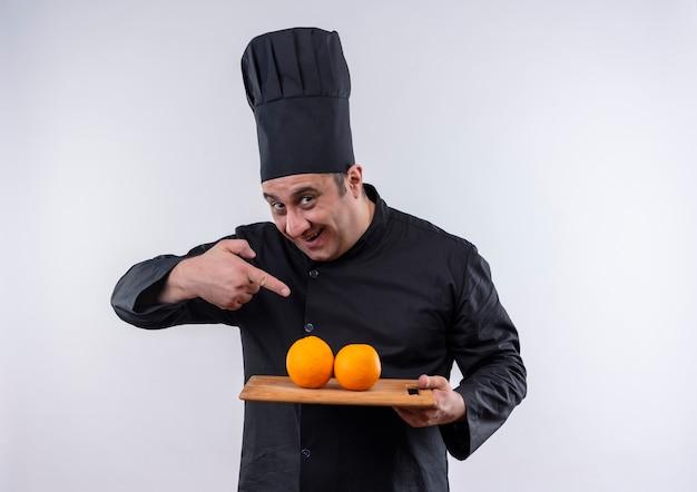 Blije mannelijke kok van middelbare leeftijd in eenvormige chef-kok wijst vinger aan sinaasappelen op scherpe raad in zijn hand op geïsoleerde witte muur