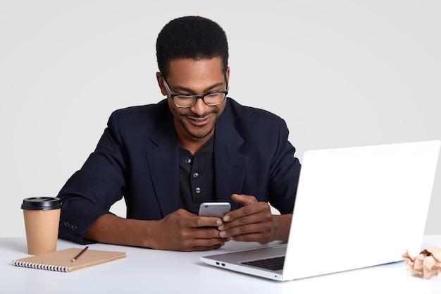 Blije mannelijke student surft sociale netwerken op mobiele telefoon, verbonden met draadloos internet, schrijft informatie op in dagboek