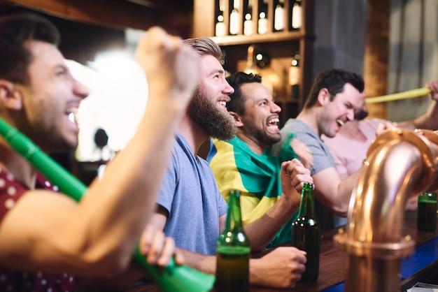 Blije mannen tijdens het kijken naar amerikaans voetbal