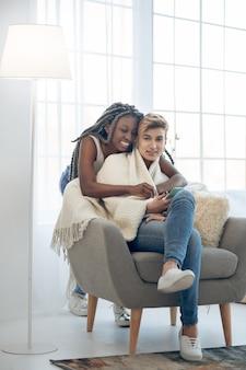 Blije meiden. afro-amerikaanse lachend meisje knuffelen haar vriendin zittend in de stoel