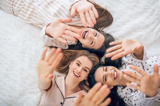 Blije meiden. drie meisje liggend in bed glimlachend en op zoek gelukkig
