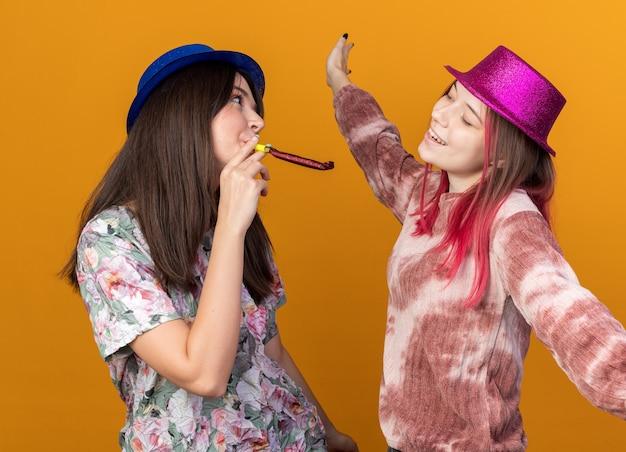 Blije meisjes met feestmuts die feestfluitje blazen, kijken elkaar aan, geïsoleerd op een oranje muur