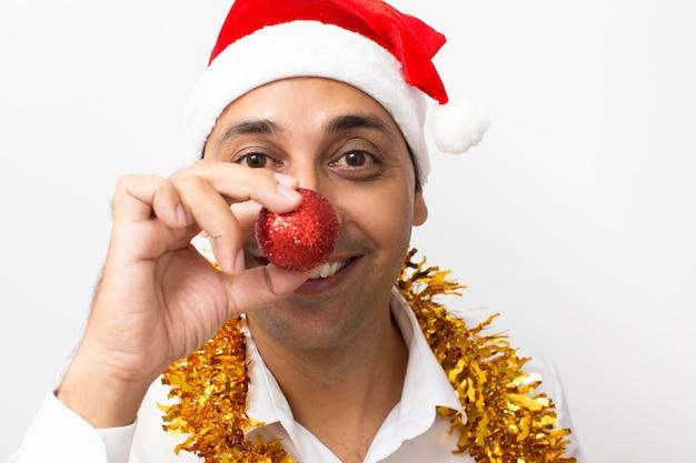 Blije mens die neus behandelt met kerstmisbal