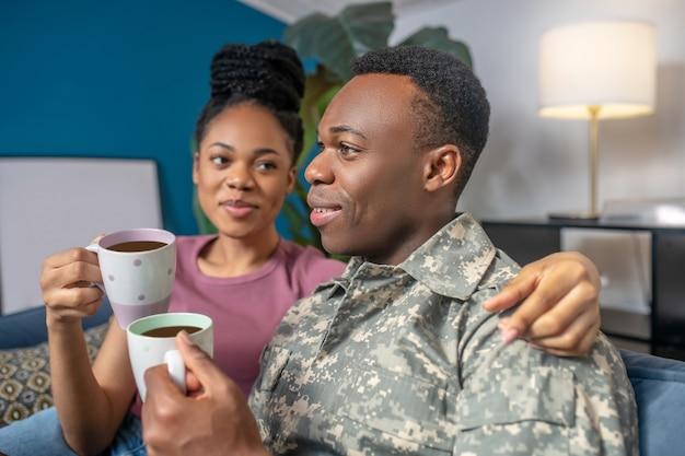 Blije mensen. afro-amerikaanse jonge vrouw knuffelen militaire echtgenoot die koffie drinkt en gelukkig thuis op de bank zit