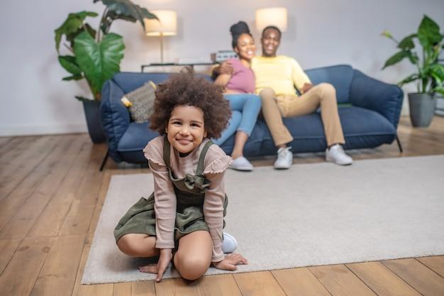 Blije mensen. donkerhuidig glimlachend dochtertje op de vloer en omhelsde jonge ouders die thuis op de bank zitten
