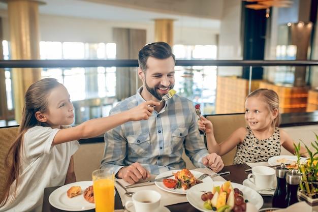 Blije mensen. glimlachende familie die aan de tafel zit en gelukkig kijkt