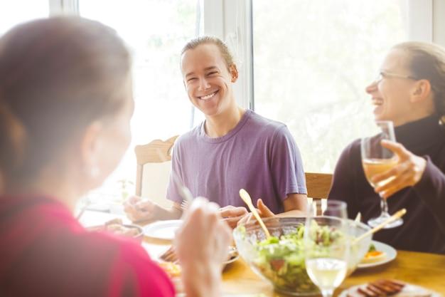 Blije mensen praten aan de keukentafel.