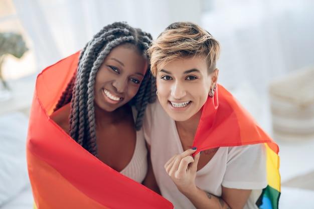 Blije mensen. twee jonge meisjes met een regenboogvlag die positief glimlachen