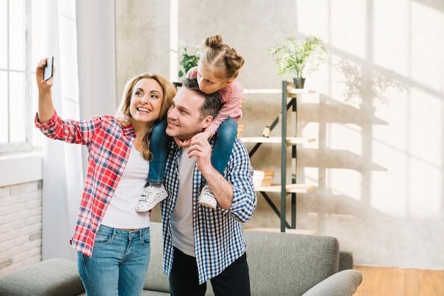 Blije moeder die selfie op mobiele telefoon nemen terwijl vader die hun dochter op schouder in woonkamer vervoeren