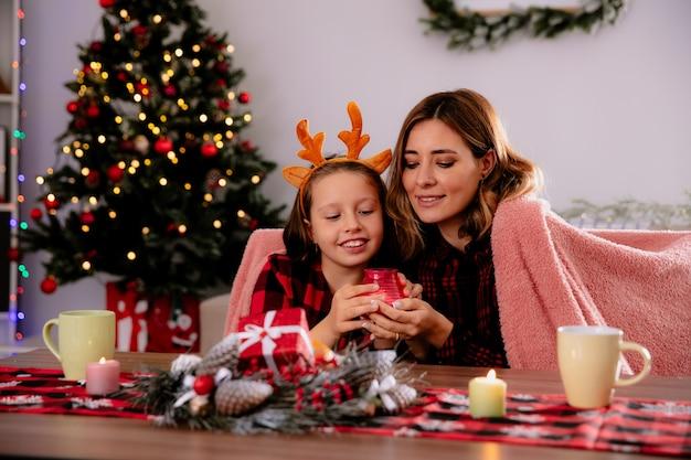 Blije moeder en dochter houden en kijken naar kaars zittend aan tafel genietend van de kersttijd thuis at