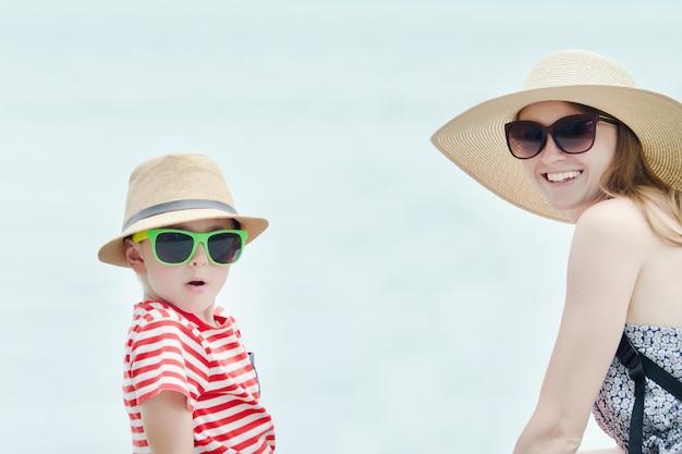 Blije moeder en zoon in hoeden en zonnebrillen. hemel op de achtergrond