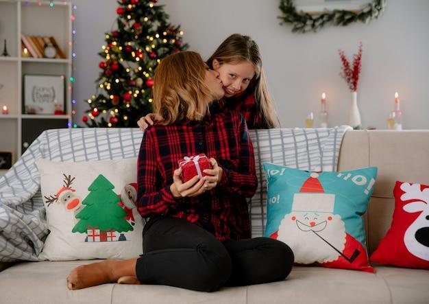 Blije moeder houdt geschenkdoos vast en kust dochter zittend op de bank en geniet thuis van de kersttijd