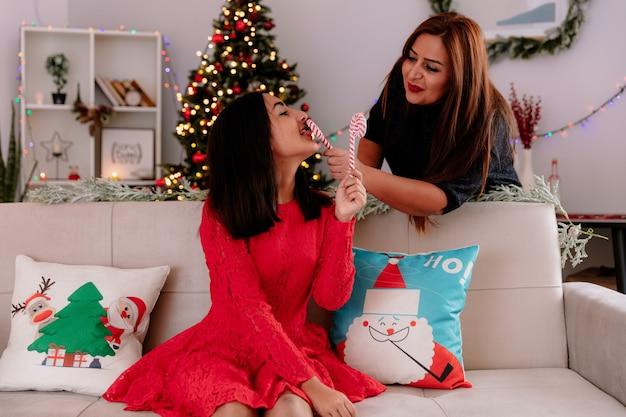 Blije moeder houdt snoepriet tegen de mond van haar dochter en ze likt snoepriet terwijl ze op de bank zit te genieten van de kersttijd thuis