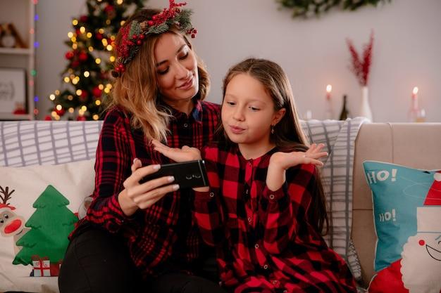 Blije moeder houdt telefoon vast en kijkt naar verwarde dochter die op de bank zit en thuis geniet van kersttijd