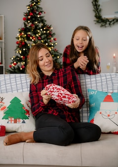 Blije moeder houdt vast en opgewonden dochter kijkt naar cadeaupakket zittend op de bank en geniet thuis van kersttijd