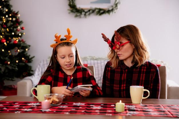 Blije moeder in rendierbril kijkt naar dochter met potlood en notitieboekje zittend aan tafel genietend van de kersttijd thuis