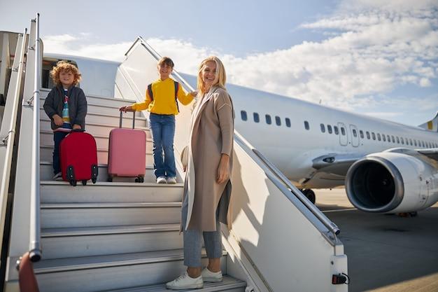 Blije moeder met haar kinderen aan boord van het vliegtuig