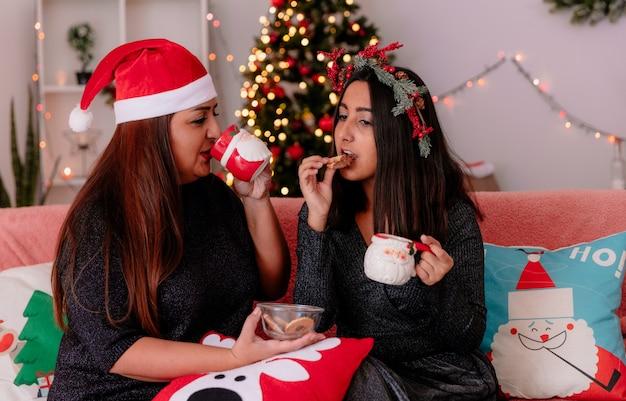 Blije moeder met kerstmuts drinkt uit beker en kijkt naar haar dochter met hulstkrans die koekje eet zittend op de bank en geniet van kersttijd thuis