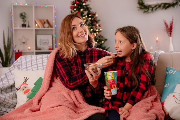 Blije moeder voedt haar dochter met koekjes zittend op de bank bedekt met deken en geniet thuis van de kersttijd