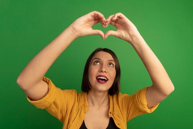 Blije mooie blanke vrouw gebaren hart handteken boven het hoofd op groen