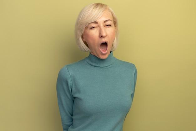 Blije mooie blonde slavische vrouw knippert oog geïsoleerd op olijfgroene muur