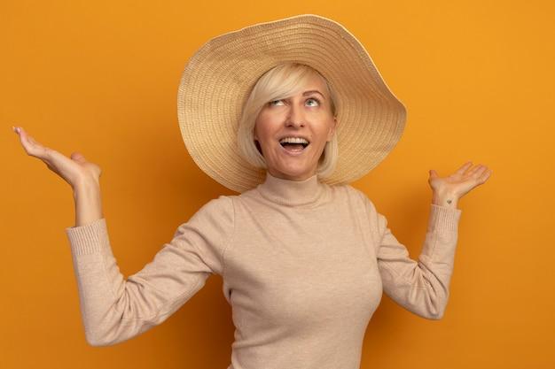Blije mooie blonde slavische vrouw met strandhoed staat met opgeheven handen die omhoog op sinaasappel kijken