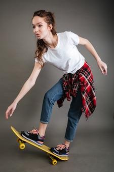 Blije mooie jonge vrouw die op skateboard berijdt en pret heeft