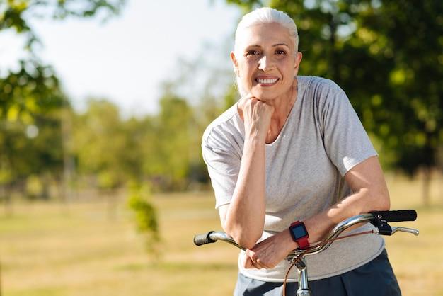 Blije mooie seniuor vrouw met stuur van haar fiets