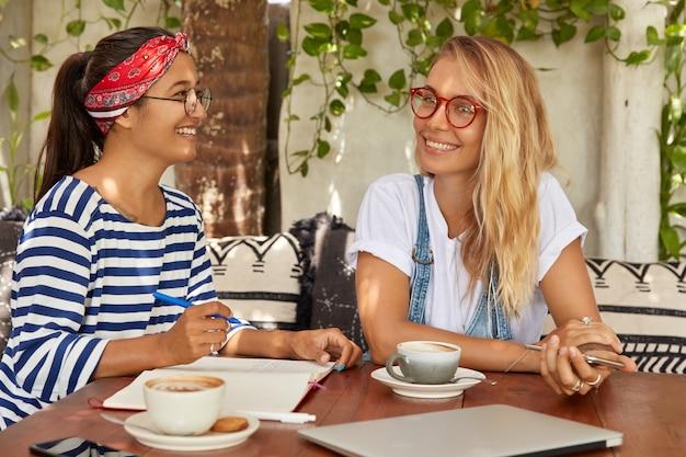 Blije multi-etnische vrouwen hebben samen plezier, lachen vrolijk