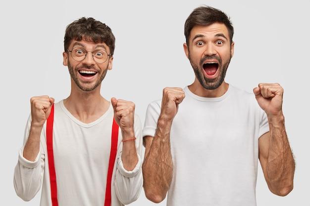 Blije ongeschoren twee jonge mannen balken vuisten en schreeuwen van geluk, terloops gekleed, geïsoleerd op een witte muur