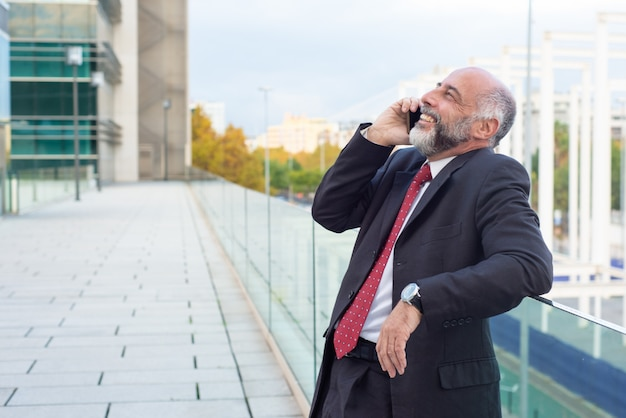 Blije ontspannen rijpe bedrijfseigenaar die op cellphone spreekt