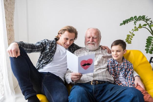 Blije opa die met de hand geschreven verjaardagswenskaart lezen