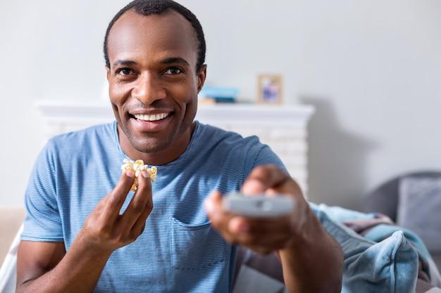 Blije opgetogen knappe man glimlachend en tv-kanaal kiezen tijdens het eten van popcorn