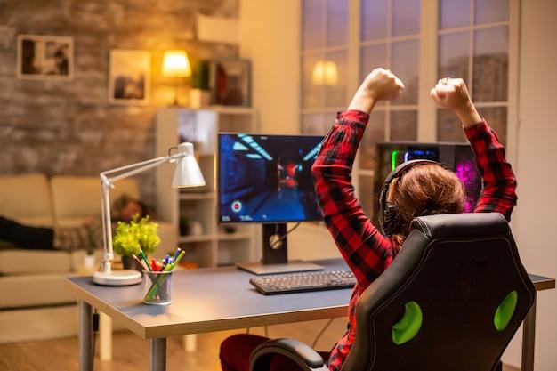 Blije opgewonden gamer die 's avonds laat in de woonkamer een online videogame wint