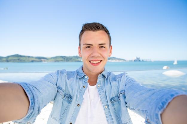 Blije opgewonden toeristenkerel die selfie op zee nemen