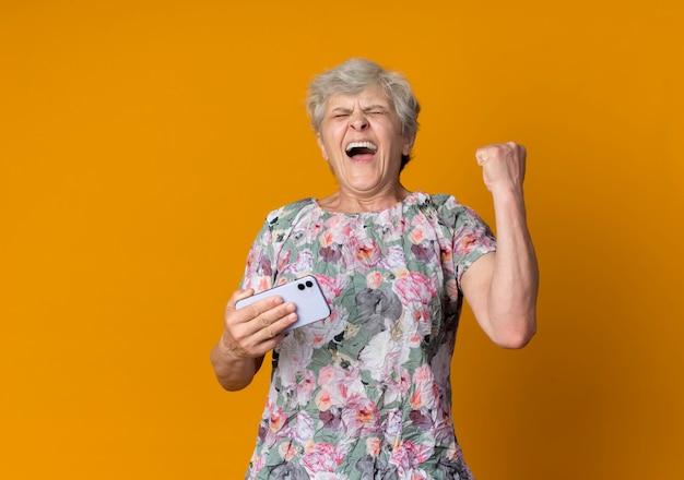 Blije oudere vrouw houdt telefoon vast en steekt vuist omhoog geïsoleerd op oranje muur