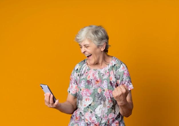 Blije oudere vrouw kijkt naar de vuist van de telefoonholding die op oranje muur wordt geïsoleerd
